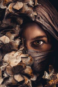 Poster van een vrouw met gezichtsbedekking in de natuur omgeven door bloemen en insecten.