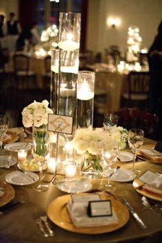 Cylinder vase centerpiece with candles and minimal flowers