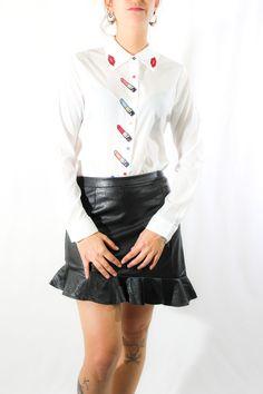 ¡La camisa más cuqui! Es muy ligera y fluída, de tacto agradable, con bordaditos de pintalabios en la línea del ojal y besitos en las solapas del cuello. Es ideal tanto para faldas como para pantalones.