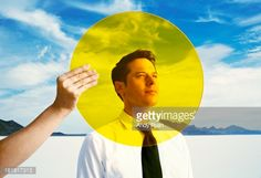 Stock Photo : Hand holding yellow circle in front of man's head.