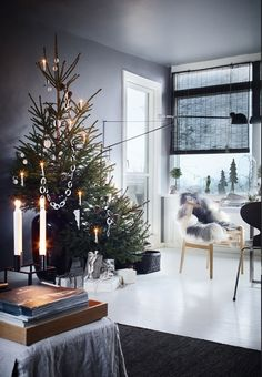 Nordic living room with an asymmetric, two-parted Christmas tree with minimalistic Christmas ornaments.