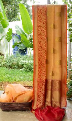 This beautifully textured Benares linen is in peach with gold zari bhuttas all over. The border and pallu are in red with intricate gold zari weaving, giving the sari a pleasant finish.