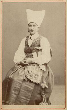 Kvinna sitter iklädd högtidsdräkt från Vingåker, Södermanland.