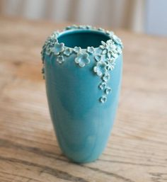 This ceramic vase is simple and pretty. The tiny flowers are detailed and repetitive which doesn't make the vase look so lonely.