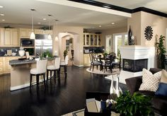 Love the color scheme and kitchen/dining room layout with that fireplace on the wall - LOVE the dark floors.