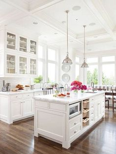 All #White Rooms: Dark wood floors ground this traditional style all white #kitchen.