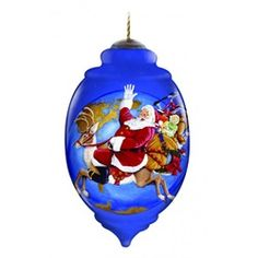 "Ne'Qwa ""Christmas Joy is All Around"" Hand-Painted Blown Glass Christmas Ornament #7131157 This beautiful, hand-made glass ornament depicts Santa on Christmas Eve, riding on his reindeer, with his bag of gifts on his back. Also features the artist's signature and an antiqued gold topper and green tassel  Artist - Joseph Holodook"