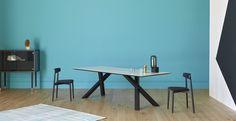Design: Paolo Cappello. Tavolo da pranzo con gambe in acciaio verniciato e piano in legno con caratteristico bordo a corteccia.