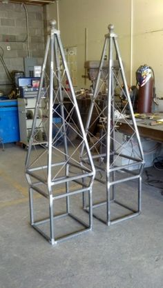 Custom made Obelisks made to fit inside a flower planter box. Vines will grow up the iron work  with flowers inside. Bottom of iron base will be in placed in the planter box. 6 feet  tall.