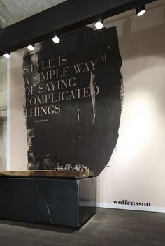 wall quote behind reception - style is a simple way of saying complicated things. black and white