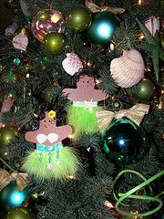 Hawaiian Ginger Bread Hula Dancers by S'mee. start with pre-cut/painted gingerbread boys (Michaels/HobbyLobby) the skirt is feathered ribbon, topped with shelled ribbon - both hot glued on; hot glue shell bikini top, Hot glue a ornament hook,hot glue curly doll hair over hook, use a permanent pen and draw the faces. Boys get just the feathers and a tiny starfish (buy in bulk from OrientalTrader)