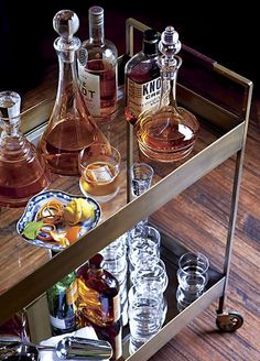 Clear top shelf serves up drinks and condiments, while decanters, bottles, and glassware sit pretty below on shelves of antiqued tempered glass. | Libations Cart from Crate Barrel