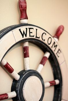 """Red white and blue wooden ships wheel makes a cute """"Welcome"""" wall decor"""