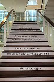 -woord-  Het gedicht van Emad Fouad is op de traptreden geplakt op de tentoonstelling 'Poëzie op de plint' in het Stadskantoor Leyweg.  De woorden van het gedicht harmoniëren met de plaats waarop het gekleefd werd.   Het gedicht neemt plaats in de ruimte in. Zowel in de hoogte als in de breedte.