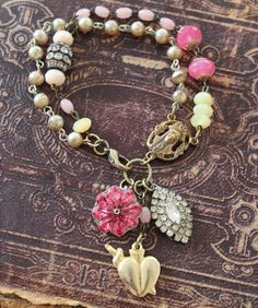 A vintage Blessed Mother rosary connector, a raspberry-hued glass flower, an authentic Mexican heart-shaped milagro and a bit of sparkle fro...
