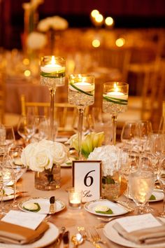 Floating Candle Centerpiece, framed table number, votive candles, and small flower bouquets