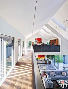 A walkway leads to Grazer's office on the mezzanine level which boasts views of the living room below | archdigest.com