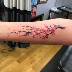 Vibrant cherry blossom tattoo on forearm by John Torres