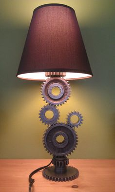 "Simple Gear Industrial Table Lamp The ""Gear Lamp"" is an Industrial Table Lamp with a Steampunk Design. The lamp is created from used gears that supplied power thru a transmission gearbox. The gears are in their unfinished original condition. Car Part Furniture, Automotive Furniture, Furniture Decor, Furniture Design, Rustic Furniture, Vintage Furniture, Vintage Lamps, Furniture Outlet, Furniture Stores"