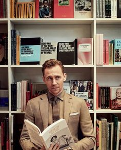 The book he is holding and the books that are behind him...