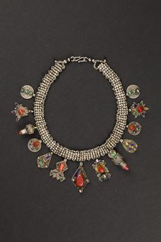 Africa | Azrar necklace, Beni Yenni. Great Kabylia, Algeria. Beginning 1900s | Double silver chain which hang Tabuhemset charms, with different shapes, decorated in varnish polychrome cloisonné and coral.