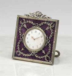 A SILVER-GILT AND GUILLOCHÉ ENAMEL DESK CLOCK MARKED FABERGÉ, WORKMASTER'S MARK OF MICHAEL PERCHIN, ST. PETERSBURG, CIRCA 1890 Square, enameled in translucent purple over a chevron guilloché ground, applied with entwined ribbon-tied laurel garlands and crossed arrows, centering a white enamel dial within a silver guilloché-chased bezel, all within a reeded border chased with laurel leaves at intervals, surmounted by a crest in the form of a bow, intertwined with a ribbon and laurel.