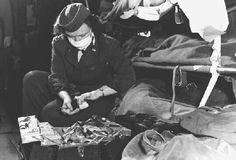 """From the U.S. Department of Defense: Flight nurse Captain Irene Wiley prepares medicine for one of her patients aboard a C-54 """"Skymaster"""" air evacuation plane en route from Okinawa to Formosa."""