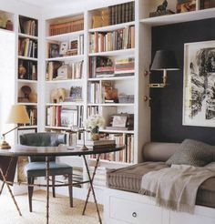 Create a sense of built-ins by using standard stand-alone bookcases and taking them as close to ceiling height as possible.  Add a crown molding to the top if its in the budget.  Notice the wall sconce attached to the bookcase - a great space saver.