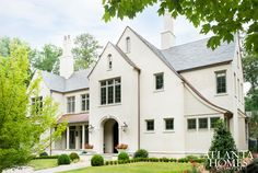A smooth stucco exterior with slate and copper roof looks sharp thanks to an Edwin Lutyens–inspired, gently sloping roof. The color palette and materials were just as important as the structure itself, says Historical Concepts' Terry Pylant, who also notes the soft gray window trim and sashes.