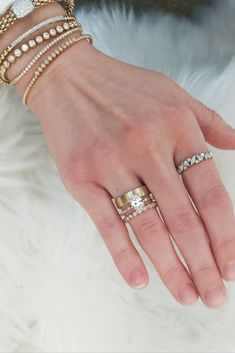 Stacked yellow gold rings and diamond bracelets. This engagement ring features an oval diamond center stone. #oval #diamond #yellowgold #gold #stacked #stackable #weddingbands #bracelets #bangles #tennisbracelet