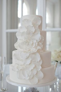 Keep things soft and classic with an all-white cake and waterfall of white petals.