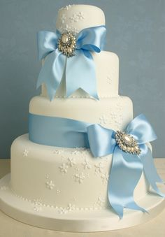 Something blue! Delicate fondant wedding cake with light blue bows and pearl brooch details. By Peggy Porschen.
