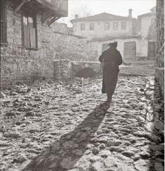 ofisofi: Εικόνες από τον ελληνοϊταλικό πόλεμο. Φωτογραφίες του Δ.Χαρισιάδη-Η σκια της μαυροφορεμένης γυναίκας αντανακλάται στο καλντερίμι του δρόμου του χωριού. Διακρίνονται τα σπίτια του χωριού.