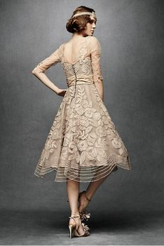 Swarovski-dotted, floral-appliqued number from Tracy Reese. Appliqued and beaded by hand, with jeweled buttons dotting the V-back and three-quarter sleeves, this bygone-era frock features a ruched band of silk taffeta at the waist and a voluminous, below-the-knee scalloped skirt. Button closure. Nylon tulle; silk slip with adjustable straps; nylon tulle and nylon horsehair hemline for soft shape.