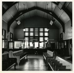 Black and white photo of the interior of the Grand Truck Western Depot in Lansing, taken in June 1968. Benches are in the foreground. In the background, a clerk stands behind a window at a counter. A 1968 Canadian National Railway calendar is hung on an adjacent window near a Western Union sign. A The State Journal newspaper rack is in front of the counter. The station's vaulted ceiling is in view at the top of frame.