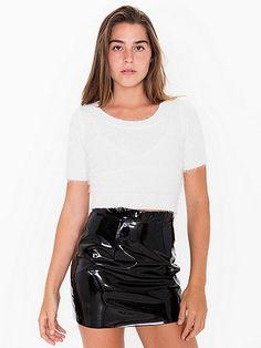 A high-waist mini skirt constructed from shiny vinyl featuring two front pleats and back zipper and clasp closure.