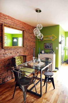 Sala de jantar com parede de tijolo e verde. Mesa em vidro, cadeiras diversas, teto branco e piso laminado em madeira.