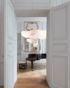 Dans le petit salon de musique, confrontation graphique entre le piano noir et les volutes de la lampe Cloud de Gehry.