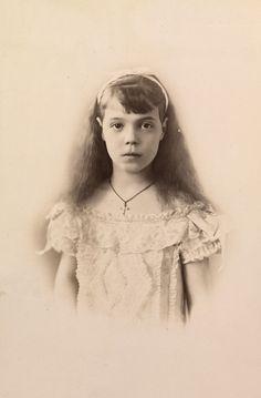 Grã-duquesa Olga Alexandrovna, em cerca de 1894. Ela está em pé de frente para a câmera e está vestindo um vestido de renda e um crucifixo.