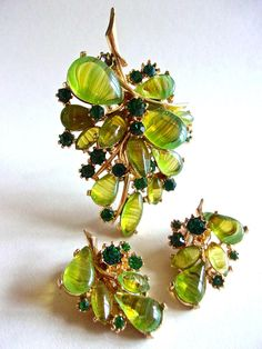 An ART signed green art glass brooch earrings set with cabochons ..... vintage  When you gaze at this set by ART, subtle green striping appears in the tear-drop and oval art glass cabochons both in the brooch and earrings. Sprinkled are prong-set emerald green rhinestones. Overall the 2-tier layer brooch shows off a leaf cluster motif in gold plating framework. On the reverse side are some open backs with an etched gold tone frame. The translucency of the cabochons gives it a lovely effect…