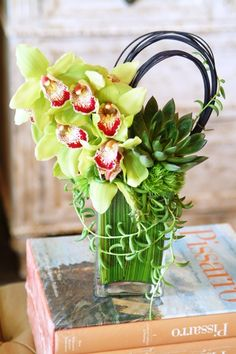 Love the mix of cymbidium green orchids and succulents in this vase.