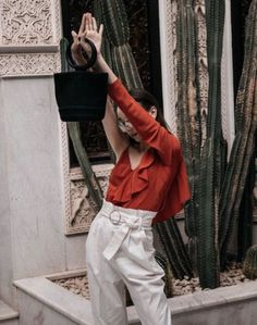 Beatrice Gutu wears the Asymmetric Ruffle Blouse. A new spin on the classic one-shoulder silhouette, this red blouse features a ruffle trim that cascades down the body from shoulder to waist and a bias cut for added fluidity. All in a 100% silk fabric with beautiful drape.