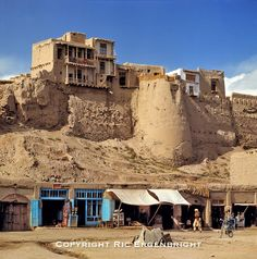 A line of merchant's stalls sit beneath the ancient wall of Ghazni, Afghanistan. ©Ric Ergenbright