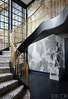 Kelly Wearstler designed a dramatic staircase with a custom brass railing for a home on Mercer Island, Washington. The wall paper is by Porter Teleo.