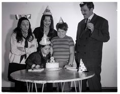 A rare behind the scenes shot of stars Carolyn Jones, John Astin, Ken Weatherwax and special guest Margaret Hamilton celebrating Lisa Loring's birthday during filming of the 1966 THE ADDAMS FAMILY TV episode, Happy Birthday Grandma Frump! The Addams Family 1964, Addams Family Tv Show, Family Tv Series, Addams Family Characters, Adams Family, Morticia And Gomez Addams, John Astin, Happy Birthday Grandma, Urban Movies