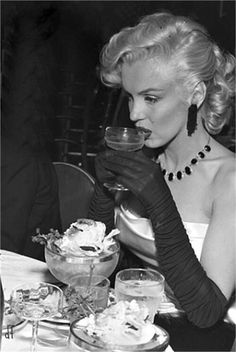 Marilyn Monroe sips in opera length black evening gloves.