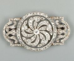 An Edwardian diamond panel brooch, circa 1905,  the central circular panel of whirl design, millegrain-set throughout with rose and single-cut diamonds, to associated lobed terminals, length 4.7cm.