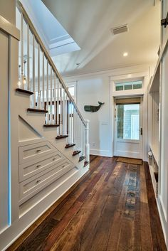 weathered wood floor in foyer with storage under stairs | coastal home | Archiscapes