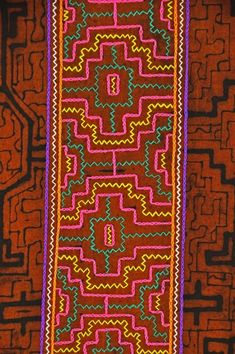 Designs combining earthen clay slip and colorful embroidery are distinctive to the Shipibo women of the Amazon basin and are used in this table runner.