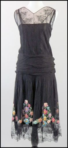 1920'S ERA BLACK SILK AND LACE OVERLAY DROP WAIST DRESS. With a ruched waist. Bearing a floral embroidery on the skirt
